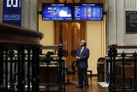 A trader looks at screens at Madrid's bourse December 7, 2011. REUTERS/Susana Vera