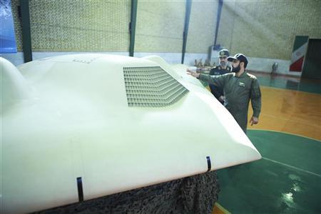 EDITORS' NOTE:   Reuters and other foreign media are subject to Iranian restrictions on leaving the office to report, film or take pictures in Tehran. An undated picture received December 8, 2011 shows a member of Iran's revolutionary guard (R) pointing at the U.S. RQ-170 unmanned spy plane as he speaks with Amirali Hajizadeh, a revolutionary guard commander, at an unknown location in Iran. The unmanned U.S. drone Iran said on Sunday it had captured was programmed to automatically return to base even if its data link was lost, one key reason that U.S. officials say the drone likely malfunctioned and was not downed by Iranian electronic warfare. REUTERS/Sepah News.ir/ Handout