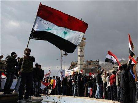 Supporters of Syria's President Bashar al-Assad wave flags during a rally at al-Sabaa Bahrat square in Damascus, December 9, 2011. REUTERS/ Stringer