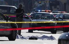 Investigador observa corpo coberto por um lençol após um tiroteio em Hollywood. Um homem armado atirou contra motoristas no centro de Hollywood, na sexta-feira, ferindo três pessoas, antes de ser morto por um policial de folga, que estava trabalhando em um set de filmagens nas proximidades. 09/12/2011  REUTERS/Mario Anzuoni