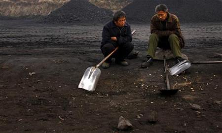 Two men take a break from loading coal onto trucks near the town of Dangcheng, in Quyang county, located 250 km (155 miles) southwest of Beijing December 7, 2011.    REUTERS/David Gray