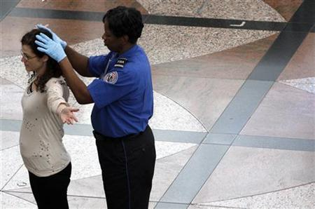 A Transportation Security Agency (TSA) worker runs her hands over the head of a traveler during a patdown search at Denver International Airport, the day before Thanksgiving November 24, 2010.  REUTERS/Rick Wilking