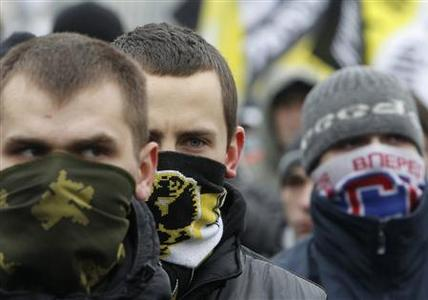 Masked nationalist activists look on during a demonstration in central Moscow December 11, 2011. On Saturday, tens of thousands gathered across Russia to express anger at the the result of recent parliamentary elections, the largest such mass opposition gathering since the end of the Soviet Union.  REUTERS/Denis Sinyakov