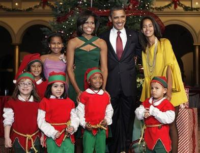 President Barack Obama, first lady Michelle Obama and their daughters Sasha (L) and Malia pose with children, dressed as elves, at the ''Christmas in Washington'' celebration at the National Building Museum in Washington December 11, 2011. REUTERS/Yuri Gripas