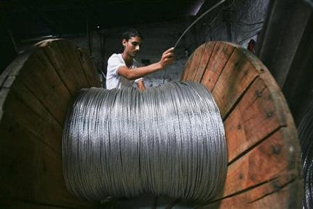 A man rolls electrical power lines onto a wooden wheel at a factory in the outskirts of Jammu September 12, 2011. REUTERS/Mukesh Gupta/Files