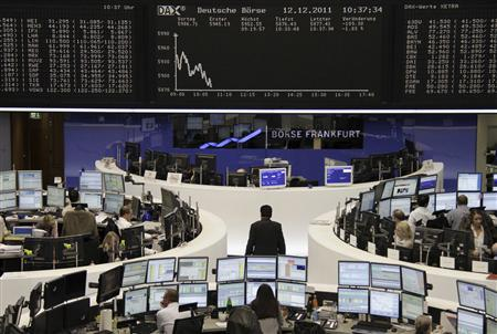 Traders are pictured at their desks in front of the DAX board at the Frankfurt stock exchange December 12, 2011. REUTERS/Remote/Sonya Schoenberger