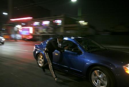 A mariachi runs next to a car offering his music to a potential client near the Plaza Garibaldi in Mexico City December 6, 2011. REUTERS/Carlos Jasso