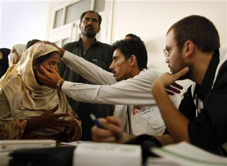 Doctors from treat a woman at an emergency medical centre for flood victims operated by Medecins Sans Frontieres (MSF) in Charsadda, located in Pakistan's northwest Khyber-Pakhtunkhwa Province August 17, 2010. REUTERS/Tim Wimborne