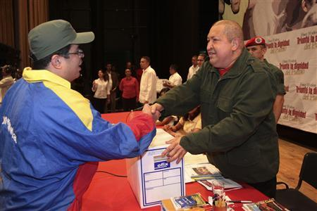 Venezuelan President Hugo Chavez (R) shakes hands with a supporter during a ceremony with his electoral alliance Gran Polo Patriotico (Great Patriotic Pole) in Caracas December 10, 2011. REUTERS/Miraflores Palace/Handout