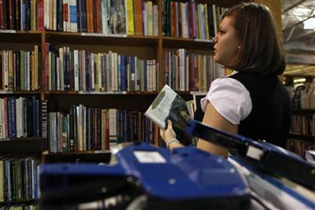 Employee Ashley Oates stocks the shelves with used books at Half Price Books in Dallas, Texas September 24, 2009.  REUTERS/Jessica Rinaldi