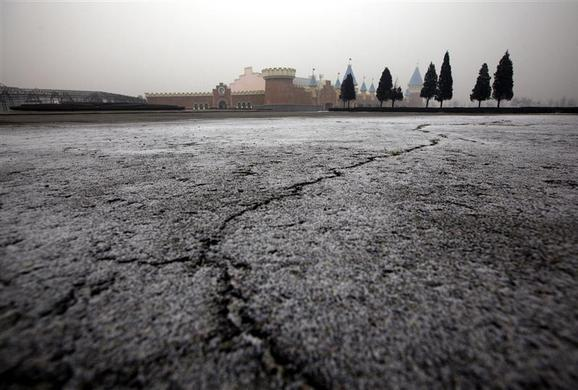 Cracks are seen in a carpark in front of abandoned buildings that were to be part of an amusement park called 'Wonderland', on the outskirts of Beijing December 5, 2011.  REUTERS-David Gray