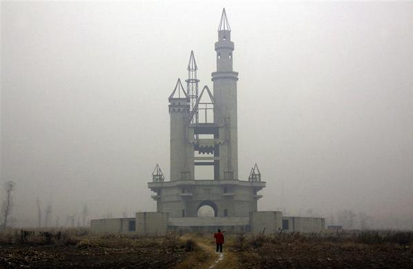A farmer carries a shovel over his shoulder as he walks to tend his crops in a field that includes an abandoned building, that was to be part of an amusement park called 'Wonderland', on the outskirts of Beijing December 5, 2011. Construction work at the park, which was promoted by developers as 'the largest amusement park in Asia', stopped around 1998 after funds were withdrawn due to disagreements over property prices with the local government and farmers.    REUTERS-David Gray