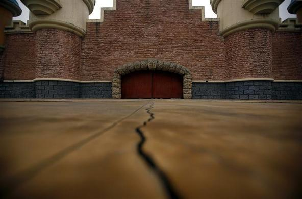 A crack is seen in a footpath leading to an abandoned building that was to be part of an amusement park called 'Wonderland', on the outskirts of Beijing December 5, 2011.  REUTERS-David Gray