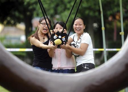 Visitors use a slingshot to shoot an Angry Bird plush toy at a real life Angry Birds outdoor game in a theme park at Changsha, Hunan province September 1, 2011.  REUTERS/China Daily