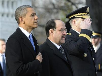 President Barack Obama (L) and Iraq's Prime Minister Nuri al-Maliki (C) stand together after laying a wreath at the Tomb of the Unknowns at Arlington National Cemetery in Arlington, Virginia, December 12, 2011.  REUTERS/Jonathan Ernst