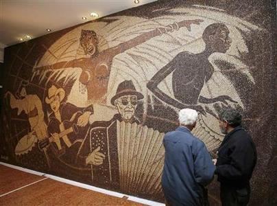 People look at a coffee bean mosaic by Albanian artist Saimir Strati in Tirana December 12, 2011. REUTERS/Arben Celi