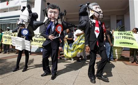 Environmental activists wearing masks with the faces of Canadian Prime Minister Stephen Harper (R) and European Commission President Jose Manuel Barroso (L) demonstrate outside a meeting of the World Business Council on Sustainable Development in Durban, December 5, 2011.  REUTERS/Mike Hutchings