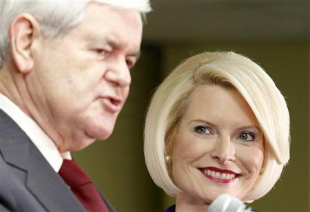 Callista Gingrich, (R) wife of Republican presidential candidate former U.S. House Speaker Newt Gingrich (L), listens to him speak to supporters during a Newt 2012 campaign office opening in Urbandale, Iowa, December 10, 2011. REUTERS/Jeff Haynes