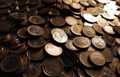 Монеты евро. Фотография сделана в Риме 9 декабря 2011 года. Евро во вторник восстановился с двухмесячного минимума к доллару, но по-прежнему уязвим, так как угроза понижения суверенных рейтингов еврозоны подрывает уверенность в единой валюте. REUTERS/Tony Gentile
