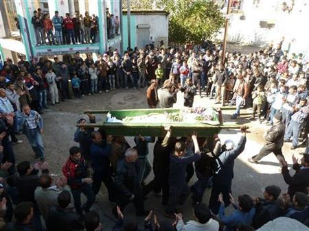 Anti-government protesters carry the coffin of Abdul Haleem Baqour during his funeral in Hula near Homs December 10, 2011. REUTERS/Handout