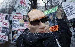 Митингующий в маске премьера Владимипа Путина на Болотной площади в Москве 10 декабря 2011 года. Огранизаторы и невольные лидеры самого массового протеста за правление Путина попытались во вторник согласовать тактику и договорились выдвинуть на следующем митинге 24 декабря прежнее требование перевыборов, но отказаться от призыва к отставке премьера. REUTERS/Sergei Karpukhin