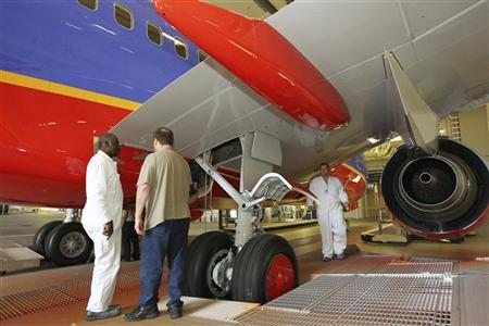 Boeing Commercial Airplanes division painters (L to R) Larry Marshall, Greg Bracelen and David Grim stand under the airframe of a Southwest Airlines 737 jetliner that has been freshly painted at the airplane manufacturer's new 737-jetliner painting facility in Renton, Washington July 13, 2011. REUTERS/Anthony Bolante
