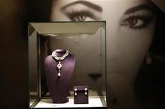 Foto de Elizabeth Taylor atrás de joias exibidas para o leilão na Christie's, em Nova York. Ricos colecionadores de jóias, cinéfilos e meros curiosos já estão treinando seus olhos para o leilão, marcado para a semana que vem, de joias, roupas e outros objetos que pertenceram à atriz Elizabeth Taylor. 01/12/2011   REUTERS/Mike Segar