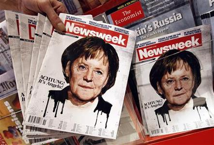 An employee of a store holds up copies of a Newsweek magazine bearing a picture of German Chancellor Angela Merkel for the photographer at the main train station in Berlin December 13, 2011. REUTERS/Fabrizio Bensch