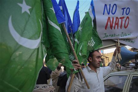 A supporter of Jamaat-e-Islami (JI), a religious and political party, holds collected party flags and placards after an anti-American demonstration in Peshawar December 2, 2011. REUTERS/Fayaz Aziz