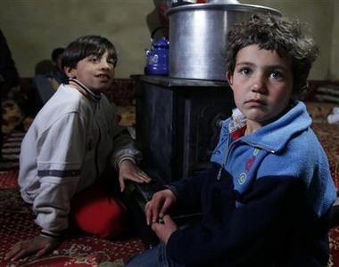 Syrian refugee children, who fled the violence in Homs, sit around a stove during an interview with Reuters in a temporary home at Aarsal town in Lebanon's eastern Bekaa, December 8, 2011.        REUTERS/Jamal Saidi