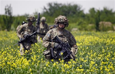 U.S. Army soldiers walk through a field during a patrol near the village of Sami Kalache in the Arghandab Valley, north of Kandahar April 15, 2011.            REUTERS/Bob Strong/Files