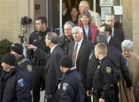 Former Penn State assistant football coach Jerry Sandusky (C, with red tie) is surrounded by police as he departs from a preliminary hearing to determine if there is enough evidence to hold him for trial on charges of sexually abusing boys, at the Centre County Courthouse in Bellefonte, Pennsylvania, December 13, 2011.  REUTERS/Pat Little