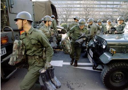 Japanese army soldiers rush between their vehicles as they get set to go underground with their gas protection gear into Kasumigaseki subway station in Tokyo in this March 20, 1995 file photo. REUTERS/Kimimasa Mayama