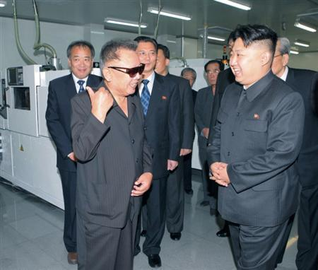 North Korean leader Kim Jong-il (front L) and his son Kim Jong-un (R) talk as they visit Mokran Video Company in Pyongyang in this undated picture released by the North's official KCNA news agency September 11, 2011. REUTERS/KCNA/Files