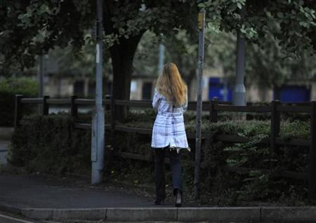 A woman is seen walking in the Thornton Road area in Bradford, northern England May 27, 2010. REUTERS/Nigel Roddis/Files