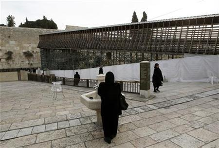 A woman stands near a footbridge that leads from the Western Wall to the compound known to Muslims as the Noble Sanctuary and to Jews as Temple Mount, in Jerusalem's Old City December 14, 2011. REUTERS/Ronen Zvulun