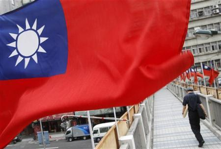 A man walks past a row of Taiwan's national flags in Taipei, October 14, 2011.    REUTERS/Pichi Chuang