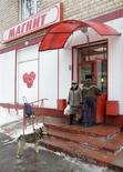 Пес наблюдает за людьми у супермаркета Магнит в Москве, 27 февраля 2010 г. Вторичное размещение акций принесло ритейлеру Магнит на $125 миллионов больше запланированного объема благодаря участию действующих акционеров. REUTERS/Sergei Karpukhin