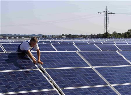 File photo of a construction worker fixing solar panels for a new solar power plant near Olching-Esting westward of Munich July 7, 2010.   REUTERS/Michaela Rehle/Files