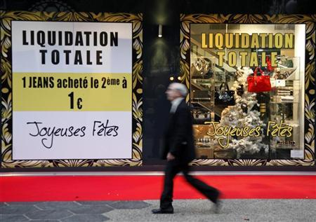 A man walks past a shop which displayed discount signs in Nice, southeastern France, December 13, 2011. REUTERS/Eric Gaillard
