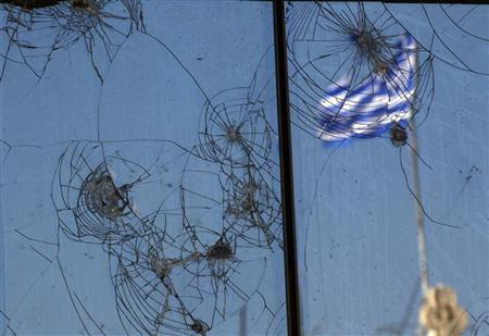A Greek flag is reflected on a glass building damaged by recent civil unrest in central Athens October 18, 2011. REUTERS/Yannis Behrakis