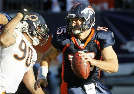 Denver Broncos quarterback Tim Tebow (R) scrambles away from Chicago Bears defensive end Julius Peppers in their NFL football game in Denver December 11, 2011. REUTERS/Rick Wilking