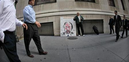 Artist Geoffrey Raymond (C), famous for his paintings of troubled Wall Street figures stands by his latest work ''Corzine Agonistes'' of former MF Global Chief and New Jersey Governor John Corzine across Broad Street from the New York Stock Exchange in New York, November 10, 2011. Corzine joins a pantheon of the famous and infamous.   REUTERS/Mike Segar