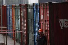 """Рабочий стоит около грузовых контейнеров в порту в Шанхае, 7 декабря 2011 года. Китайских экспортеров ждет """"очень суровая"""" обстановка в первом квартале 2012 года, так как европейский кризис затягивается и ухудшает спрос, сообщило в четверг министерство торговли страны. REUTERS/Aly Song"""