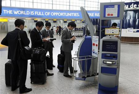 Passengers queue to use a British Airways check-in machine in the departure lounge of Terminal Five at Heathrow Airport in London October 29, 2010. REUTERS/Paul Hackett