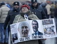 Женщина держит плакат с портретами Владимира Путина и президента Дмитрия Медведева на митинге на Болотной площади в Москве 10 декабря 2011. Премьер-министр РФ Владимир Путин, планирующий вернуться в президентское кресло в марте 2012 года, общается в прямом эфире с гражданами. REUTERS/Sergei Karpukhin