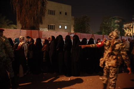 Army soldiers organise the crowd as women wait to vote at a polling booth during the second day of parliamentary elections in Suez, December 14, 2011.  REUTERS/Asmaa Waguih