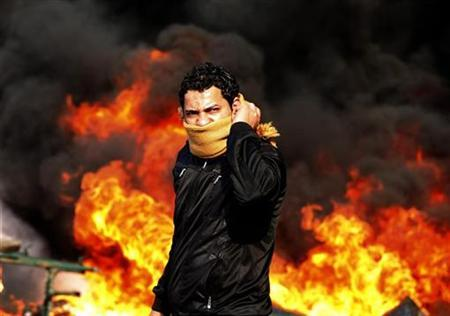 A protester stands in front of a burning barricade during a demonstration in Cairo, January 28, 2011. REUTERS/Goran Tomasevic