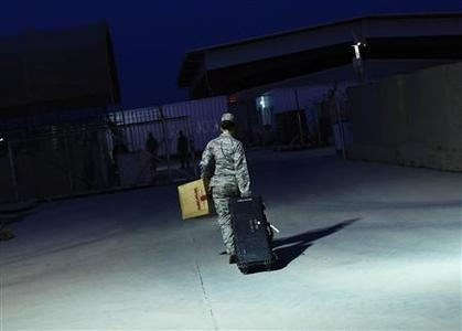 U.S. Air Force Major Stacie Shafran carries her luggage to a loading paddock while waiting for her departure from Iraq at the former U.S. Sather Air Base near Baghdad, Iraq December 14, 2011.  REUTERS/Shannon Stapleton