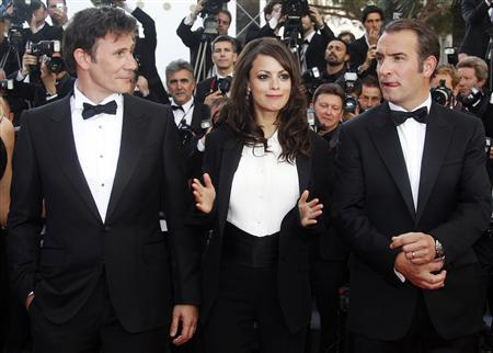 Director Michel Hazanavicius (L) poses with cast members Jean Dujardin (R) and Berenice Bejo as they arrive on the red carpet for the screening of ''The Artist'' at the 64th Cannes Film Festival, May 15, 2011.  REUTERS/Christian Hartmann